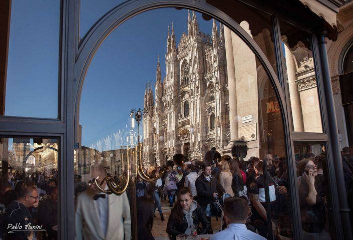 Milan's cathedral front façade reflecting on a terrase glass while the crowd is passing by. Pablo Munini