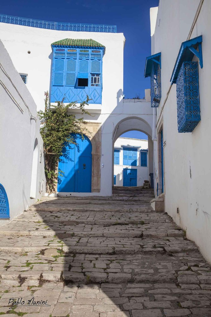 street scene Sidi Bou Said Tunisia Arches, cobbled streets shadows. White blue village. dazzling white walls and staircases, uniform shade of vivid blue.