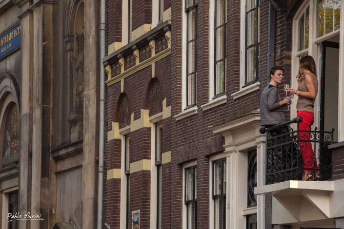 dutch women enjoying a glass of wine and the view of Amsterdam from a balcony.Pablo Munini Photography