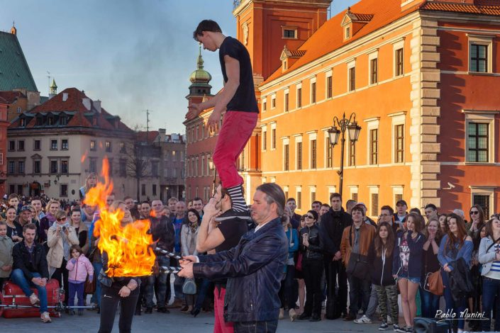 Street performer thrillsing crowd fire torches Royal Castle Warsaw,. Best photos Warsaw. main touristic attractions Warsaw.Juggler blazing torches .Life in Warsaw, people Warsaw,Phoenix city Warsaw Photography Old town market square, Sigismund's Column ,Barbican,